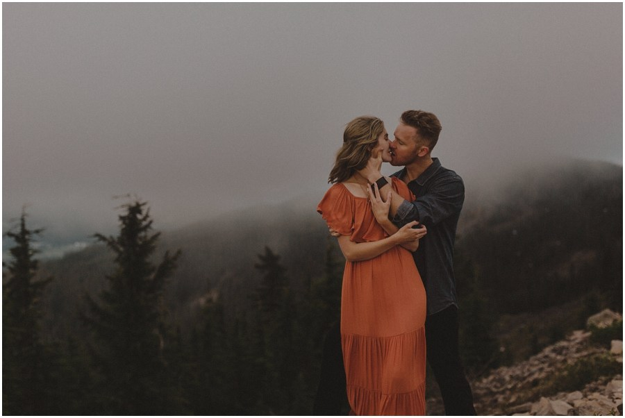 a woman in an orange dress being kissed by her husband