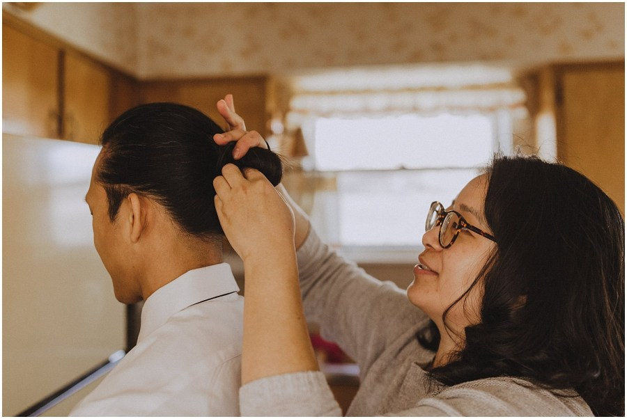 woman helping a groom tie his hair into a ponytail Chicago wedding photographer kyle szeto