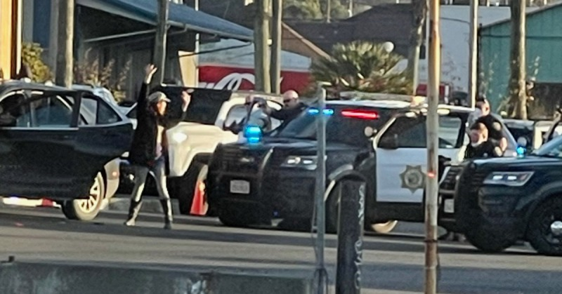 One of the travelers in the vehicle is ordered to walk backward towards officers with their guns drawn. [Photo from a reader]