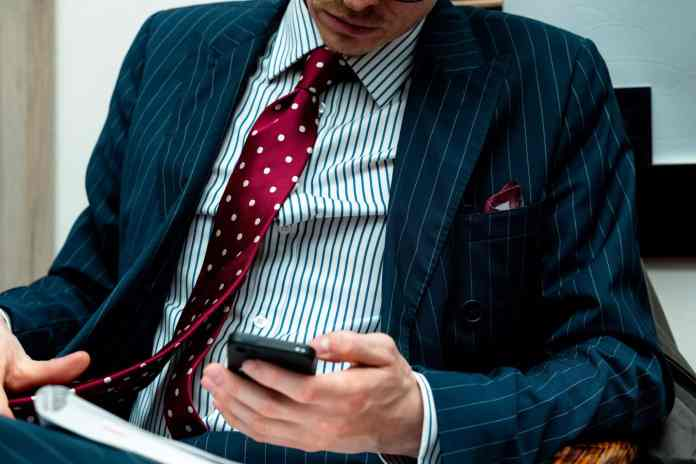man in blue suit jacket holding black smartphone