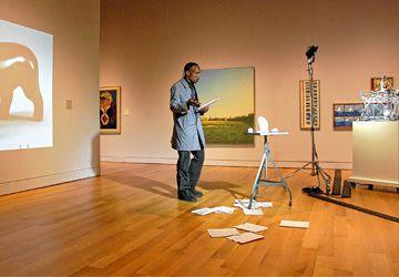 Mindbender Supreme (ci-dessus) lit un poème devant les sculptures de Mohamed Bourouissa, pendant que ce dernier passe des photos d'art inuit et que l'imprimante 3D, la machine posée sur le meuble à roulettes, imprime un nouvel objet.
