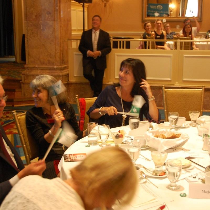 Dyane Adam (à g.) à la table d'honneur du Club canadien de Toronto, agitant un drapeau vert et blanc en anticipation du Jour des franco-ontariens (25 septembre).
