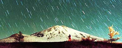 Leonid meteors are seen streaking across the sky over snow-capped Mount Fuji early Monday Nov. 19, 2001. (AP)