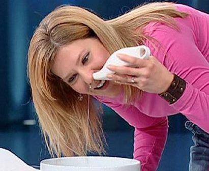 Image of a woman using a neti pot.