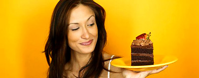 Photo by Corbis (Woman Eyeing a Slice of Chocolate Cake)