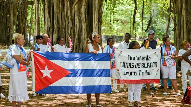 Cuban dissidents and members of the Ladies in White human rights group hold a national flag and pictures of imprisoned dissidents as they protest against the reopening of the US embassy on the island, in Havana, on August 9, 2015