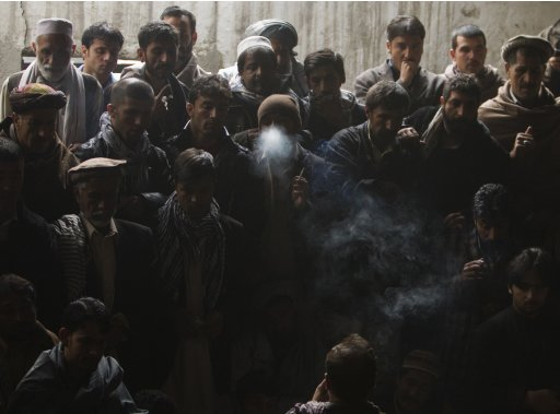 A man smokes as he watches a quail fighting competition in Kabul