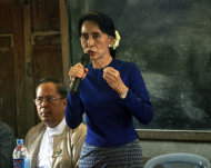 Myanmar opposition leader Aung San Suu Kyi speaks during a meeting with villagers at a primary school during a visit to an area near the Letpadaung copper mine, in Monywa township, 760 kilometers (450 miles) north of Yangon, central Myanmar, Wednesday, March 13, 2013. Opponents of the nearly $1 billion copper mine in northwestern Myanmar expressed outrage Tuesday over a government-ordered report that said the project should continue and that refrained from demanding punishment for police involved in a violent crackdown on protesters. Suu Kyi chaired the investigation commission that produced the report, which was released Monday night. (AP Photo/Khin Maung Win)
