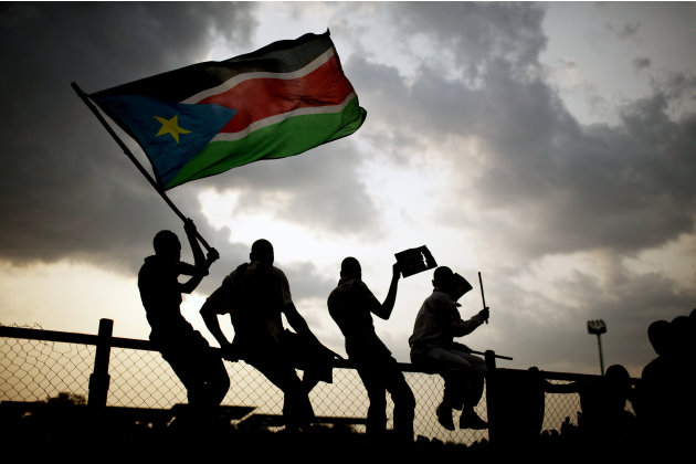 Southern Sudanese wave flags and cheer at the Republic of South Sudan's first national soccer match in the capital of Juba on Sunday, July 10, 2011. The game, played against Kenya, comes just one day