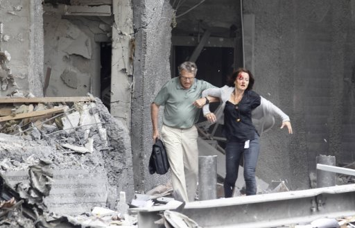 An injured woman is assisted from a damaged building in Oslo, Friday July 22, 2011, after an explosion rocked the capital. Terrorism ravaged long-peaceful Norway on Friday when a bomb ripped open buildings including the prime minister's office and a man dressed as a police officer opened fire at a nearby island youth camp. (AP Photo/Scanpix, Morten Holm) NORWAY OUT