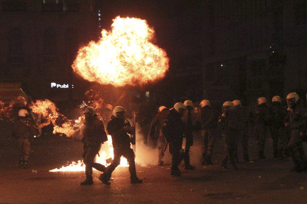 A petrol bomb explodes over riot police during clashes in Athens, Sunday, Feb. 12, 2012. Riots engulfed central Athens and at least 10 buildings went up in flames in mass protests late Sunday as lawma