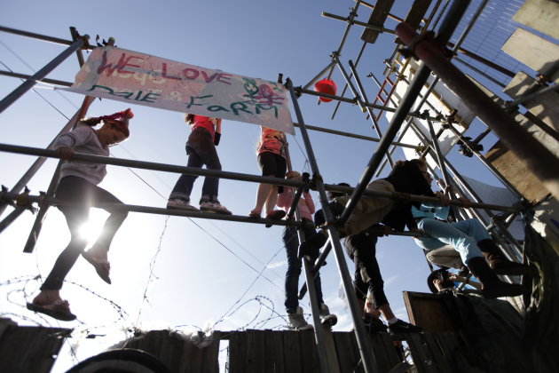 Irish Travelers, residents of the Dale Farm settlement, stand on a tower of scaffolding poles at the entrance to the site near Basildon, England, Monday, Sept. 19, 2011. Irish Travelers built barricad