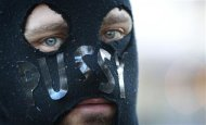 A masked man attends a rally, in support of Russian punk band Pussy Riot, in Sydney August 17, 2012. REUTERS/Daniel Munoz