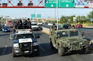 Federal police officers, left, and soldiers patrol in Monterrey, Mexico, Monday, Aug. 29, 2011. Police in northern Mexico arrested five alleged members of the Zetas drug cartel suspected of setting a casino fire that killed 52 people, authorities said Monday. (AP Photo/Hans-Maximo Musielik)