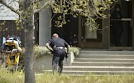 An Oakland police officer approaches the entrance to Oikos University in Oakland, Calif., Monday, April 2, 2012. A suspect was detained Monday in a shooting attack at a California Christian university that sources said has left at least five people dead. (AP Photo/Noah Berger)