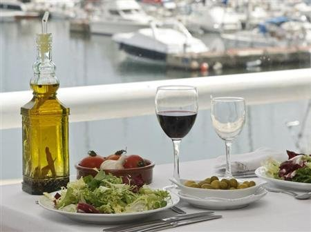 Food is seen on a table at a restaurant at the port of El Masnou, near Barcelona May 16, 2008. REUTERS/Albert Gea