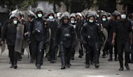 Egyptian riot police march during clashes with protesters, not seen, near Tahrir Square in Cairo, Egypt, Wednesday, Jan. 30, 2013. Egypt's liberal opposition leader called for a broad national dialogue with the Islamist government, all political factions and the powerful military on Wednesday, aimed at stopping the country's eruption of political violence that has left scores dead in the past week. (AP Photo/Khalil Hamra)