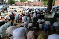 Muslims pray facing the palace of Shehu of Bornu, the traditional ruler of Bornu, despite threats by the Islamist group Boko Haram in Nigeria. The country on Wednesday lifted a state of emergency it imposed six months ago in four states following a wave of attacks blamed on the radical Islamist group Boko Haram. (AFP Photo/Pius Utomi Ekpei)
