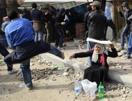 A female opposition supporter takes shelter while providing water during rioting with pro-Mubarak demonstrators near Tahrir Square in Cairo in this February 3, 2011 file photo.   REUTERS/Goran Tomasevic/Files