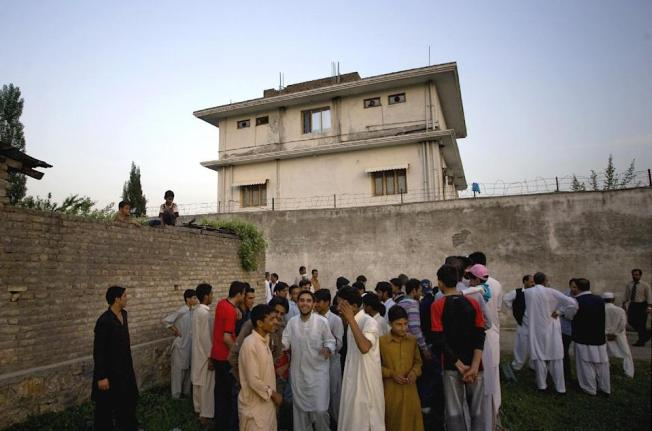 FILE - In this May 3, 2011 file photo, local residents gather outside a house, where al-Qaida leader Osama bin Laden was caught and killed in...