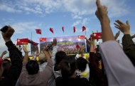 Supporters of opposition leader Aung San Suu Kyi applaud as she appears to address a public meeting at a nearby village close to Letpadaung mine in Monywa, northwestern Myanmar, Friday, Nov. 30, 2012. Opposition leader Suu Kyi has publicly criticized the forcible crackdown on protesters at a mine in northwestern Myanmar, saying the public needs an explanation of the violence that injured dozens, including Buddhist monks. (AP Photo/Gemunu Amarasinghe)