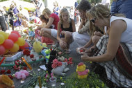 People place candles, toys and flowers at the port of Kazan, Russia, Tuesday, July 12, 2011, on the Volga River, in central Russia. Russia is observing a day of mourning for victims of a cruise ship sinking as divers work deep underwater in a Volga River reservoir to try to find more bodies. (AP Photo/Misha Japaridze)