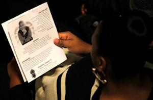 A mourner reads the obituary from the program during …