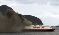 Norwegian cruise ship, MS Nordlys, one of the Hurtigruten ships billows smoke as it approaches Alesund in western Norway, Thursday Sept. 15, 2011. Passengers were forced to evacuate a popular cruise off Norway's craggy western coast on Thursday when a fire in the engine room killed two crew members and sent heavy smoke billowing through the ship. Operator Hurtigruten ASA said nine other crew were taken to hospital, two with serious burns and smoke injuries. All 207 passengers _ and most of the crew of 55 _ on board the MS Nordlys were taken to safety. Danielle Passebois-Paya, a French tourist, told Norwegian daily Aftenposten that the evacuation went smoothly. (AP Photo/Scanpix, Svein Ove Ekornesvag) NORWAY OUT