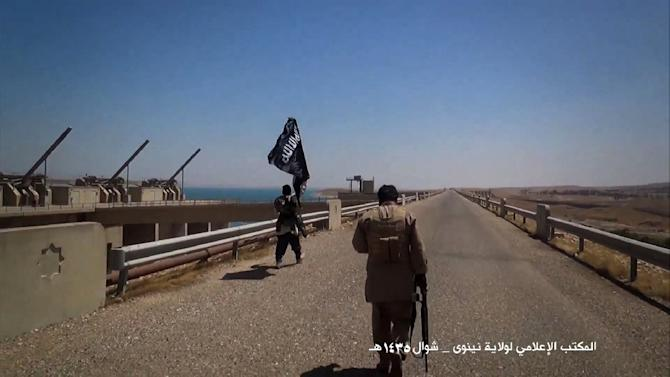 An image taken from a video released by Welayat Nineveh Media Office on August 9, 2014, allegedly shows Islamic State militants waving the trademark Jihadits flag as they inspect the grounds of the Mosul dam in Iraq