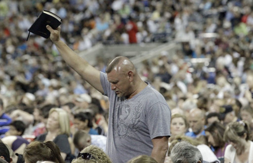 A man raises his Bible as he prays at The Response, a call to prayer for a nation in crisis, Saturday, Aug. 6, 2011, in Houston. Texas Gov. Rick  Perry attended the daylong prayer rally despite criticism that the event inappropriately mixes religion and politics. (AP Photo/David J. Phillip)