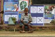 FILE - In this July 22, 2011 file photo, an elderly Sri Lankan ethnic Tamil man sits against a wall pasted with election propaganda of Sri Lankan president Mahinda Rajapaksa's ruling party in Jaffna, Sri Lanka. The road blocks have been dismantled, the sandbags removed, and Sri Lanka is again a palm-fringed tourist paradise, the government says. But for ethnic Tamils living in the former war zone in the north, it is still a hell of haunted memories, military occupation and missing loved ones. (AP Photo/Eranga Jayawardena, File)