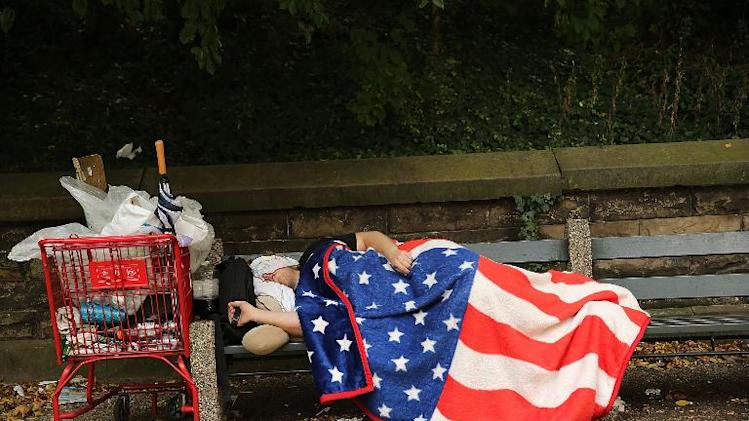 A homeless man sleeps under an American Flag blanket on a park bench on September 10, 2013 in the Brooklyn borough of New York City