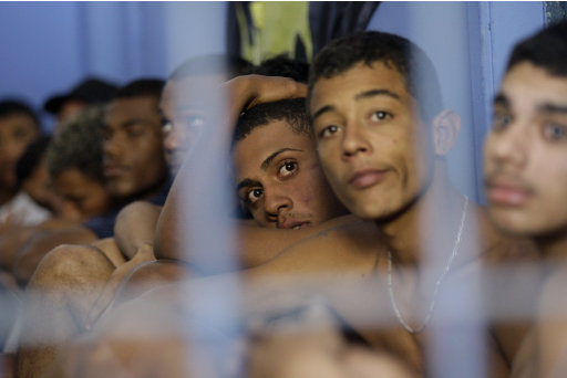 In this photo taken Thursday, July 14, 2011, young men are kept in Police custody after an anti-drug trafficking operation at the Corea favela in Rio de Janeiro, Brazil. The Brazilian city that will host the 2016 Olympic Games has one of the deadliest police forces on the planet and Juan Moraes' killing is an example of how serious the problem is. In the last five years, officers in Rio have killed on average 3.5 people per day, according to an Associated Press analysis of police data. The four police officers suspected in Moraes' death have 37 on-duty killings among them, according to police records. (AP Photo/Silvia Izquierdo)