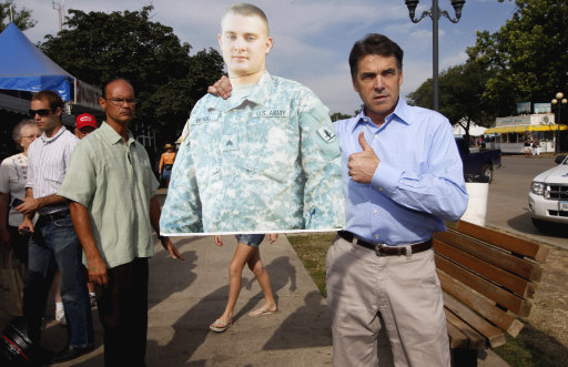 Republican presidential candidate, Texas Gov. Rick Perry poses with a cut out of U.S. Army Reserves Spc. James Benal of the Nebraska National Guard, serving in Afghanistan, after he was approached by his mother Patty Benal, as Perry visited the Iowa State Fair in Des Moines, Iowa, Monday, Aug. 15, 2011. (AP Photo/Charles Dharapak)