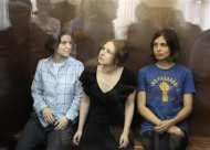 """Members of the female punk band """"Pussy Riot"""" (R-L) Nadezhda Tolokonnikova, Maria Alyokhina and Yekaterina Samutsevich sit in a glass-walled cage during a court hearing in Moscow, August 17, 2012. A Russian judge delivers a verdict on Friday against three members of the Pussy Riot punk band whose trial for staging an anti-Kremlin protest in a church has provoked an international outcry against President Vladimir Putin. REUTERS/Sergei Karpukhin"""