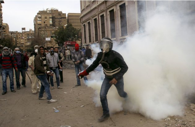 Protester returns a gas canister during clashes with security forces near the Interior Ministry in Cairo