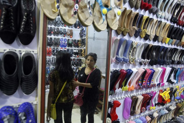 Women are reflected in a mirror as they shop for shoes at a retail store in Mumbai