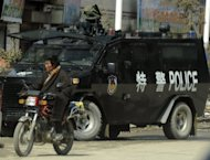 A Tibetan rides past a police armoured personnel carrier in China's northwest Qinghai province in March 2012. Two young Tibetans in a remote area of northwest China set themselves alight, state media and a rights group said Thursday, in the latest such protest against Chinese rule