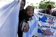 People holding cut-out masks of German Chancellor Angela Merkel, European Commission head Jose Manuel Barroso and Cypriot President Nicos Anastasiades take part in a rally protesting against an EU bailout deal in Nicosia on March 18, 2013. Protesters registered their anger at the unprecedented tax, not asked of other eurozone countries that have sought rescue