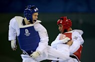 Aaron Cook (blue) of Britain lands a back kick on Anju Jason (red) of Marshall Islands during the 2008 Beijing Olympic Games. Cook, the European champion, will not be part of hte UK team in London. (AFP Photo/Jung Yeon-Je)