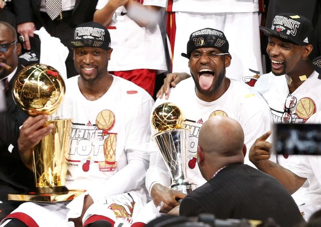 Heat's James holds the Bill Russell MVP Trophy as Wade (L) holds the Larry O'Brien Trophy while Bosh celebrates after their team defeated the Spurs in Game 7 to win their NBA Finals basketball playoff