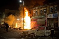 A shop and police car burn as riot police try to contain a large group of people on a main road in Tottenham, north London on August 6, 2011