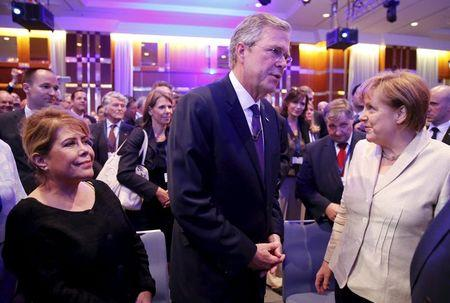 German Chancellor Merkel talks former Florida Governor and potential Republican presidential candidate Bush and his wife Columba after he addressed...