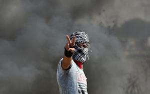 A Palestinian protester flashes the sign for victory…