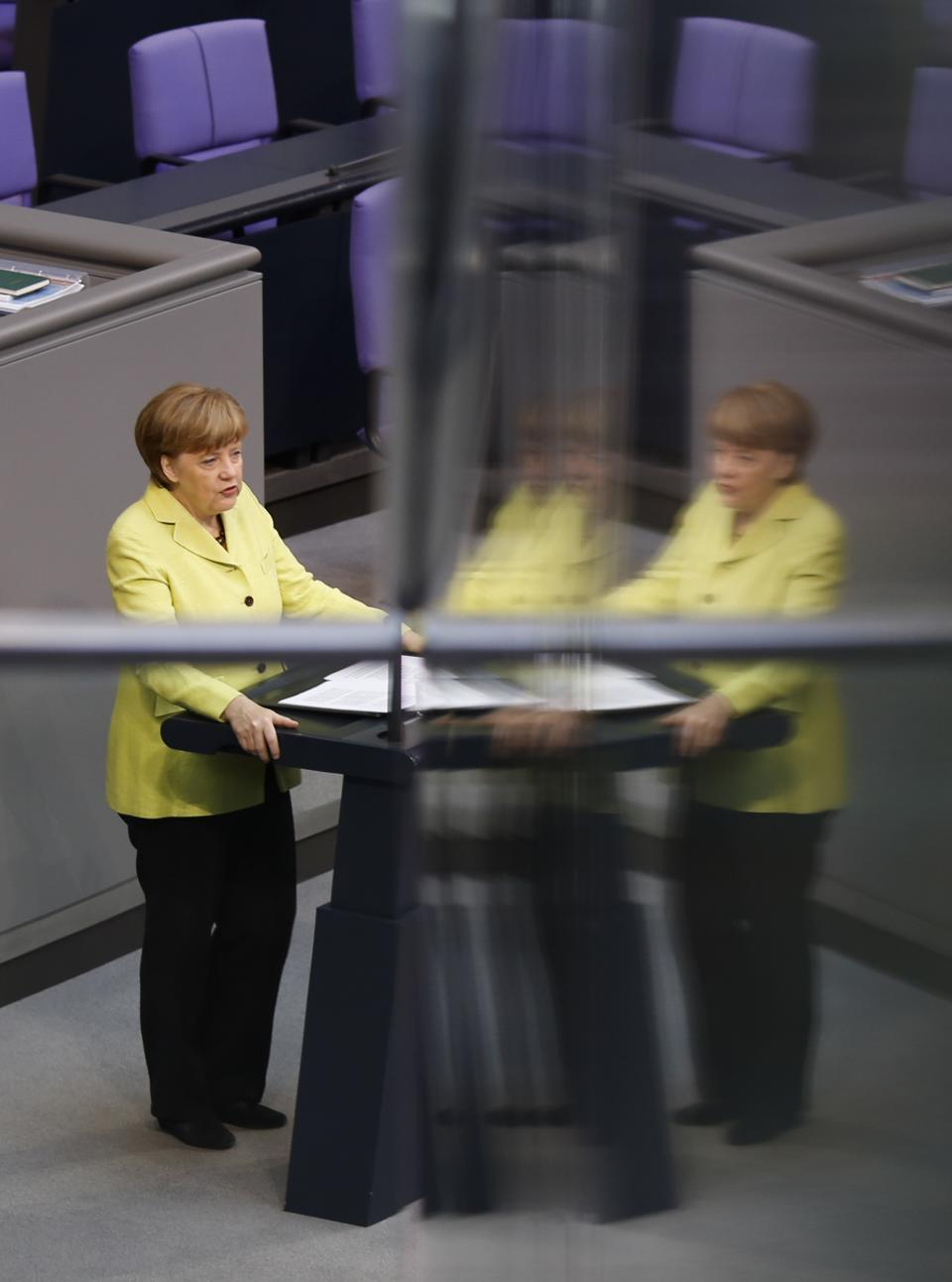 German Chancellor Angela Merkel is reflected in a window pane as she delivers a government declaration about the European Union and an Eastern...