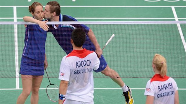 Russia's Alexandr Nikolaenko (R) kisses his partner Valeria Sorokina (L) after victory during their badminton mixed doubles match against Great Britain's Chris Adcock (front L) and Imogen Bankier
