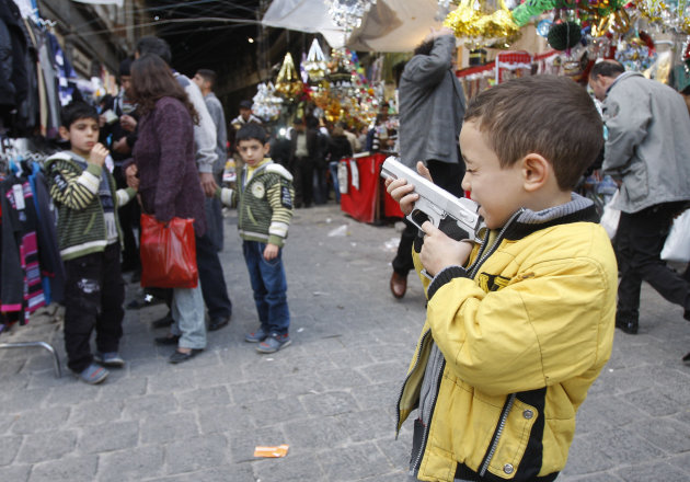 A Syrian boy plays with his toy gun, in the old city of Damascus, Syria, Saturday Nov. 5, 2011. The head of the Arab League warned Saturday that the failure of an Arab-brokered plan to end the violenc