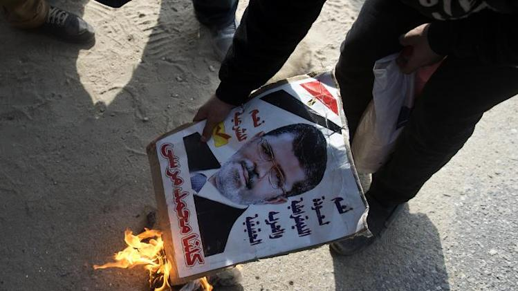 An opponent of the Muslim Brotherhood sets fire to a portrait of ousted president Mohamed Morsi on January 8, 2014 in Cairo
