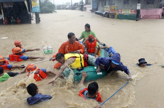 Rescuers pull a rubber boat as they evacuate residents from their flooded homes in Marikina, Metro Manila August 7, 2012. Deadly torrential rains submerged much of the Philippine capital and surrounding areas on Tuesday, forcing nearly 270,000 people to flee their homes with more flooding expected in the north of the country as a tropical storm passes through the region, officials said.   REUTERS/Erik De Castro (PHILIPPINES - Tags: ENVIRONMENT DISASTER SOCIETY)