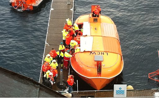 Passengers are landed from a lifeboat after a fire on the Norwegian cruise ship, MS Nordlys, one of the classic Hurtigruten ships in Alesund in western Norway, Thursday Sept. 15, 2011. The Sunnmore police district says that 106 passengers were evacuated into lifeboats before the vessel managed to dock into the port of Alesund. The rest of the passengers and crew were being evacuated. Police said no one was killed but three people were taken to hospital. The fire broke out in the engine room at 9.20 a.m. (0720 GMT). (AP Photo/Scanpix)  NORWAY OUT